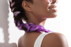 Positive young woman is enjoying her modern purple pigtails stock photo