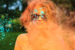 Positive young model having fun in a cloud of orange dry powder, celebrating Holi colors festival stock photography
