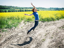 Positive young woman is jumping in rapeseed field Royalty Free Stock Images