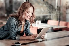 Positive young woman looking at her modern tablet and smiling. New gadget. Cheerful positive young woman leaning on the table while looking at the screen of her Stock Photography