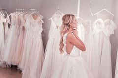Positive young woman looking at the wedding dresses. Wedding dress salon. Positive young woman looking at the wedding dresses while being in the wedding boutique royalty free stock photo