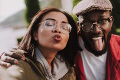 Positive young woman making faces with her boyfriend. Emotional young women making selfies with her afro American boyfriend while having fun together royalty free stock photos