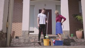 Positive young woman putting on the apron and the man giving her the mop on the porch of the house. Couple cleaning the. Positive young woman putting on the stock footage