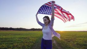 Positive young woman runs with an USA flag across a field at sunset. Positive young woman runs with an American flag across a field at sunset stock video footage