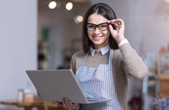 Positive young woman smiling and holding laptop. I like my business. Pretty glad young woman smiling and touching her glasses while holding laptop royalty free stock photography