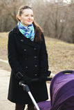 Positive young woman with stroller. Looking sideways Stock Photography