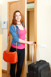 Positive young woman with suitcase near door Stock Images