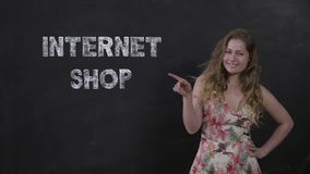 Beautiful girl makes purchases at home. Online shopping concept. Positive young woman in a summer dress on a black background with the words internet shop stock video footage