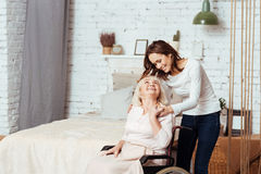 Positive young woman taking care of her grandmother in wheelchair. Nice carer. Joyful delighted old women sitting in wheelchair and lookign at her granddaughter Stock Photo