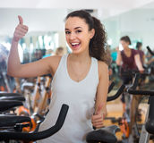 Positive young woman training on exercise bikes Stock Photo