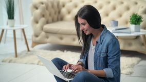 Positive young woman using her laptop. With pleasure. Cheerful young woman sitting on the floor and using her laptop while resting at home stock video