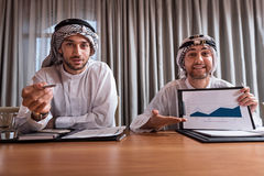 Positively spirited partners while working. Look at this. Positive handsome men presenting the diagram to the manager and another one adding some information to Stock Image
