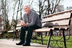 Positiver älterer Mann, der auf Audio hört lizenzfreie stockfotos
