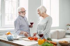 Positiver älterer Mann, der ein Glas Wein hält lizenzfreie stockfotos