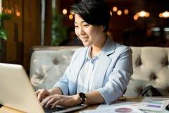 Positiver asiatischer Manager, der Bericht im Café vorbereitet stockfoto