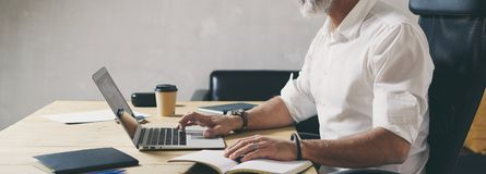 Positiver bärtiger Geschäftsmann unter Verwendung der mobilen Laptop-Computers beim Sitzen am Holztisch am modernen coworking Pla lizenzfreie stockbilder