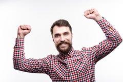 Positiver bärtiger Mann, der seine Hände nach Erfolg anhebt lizenzfreie stockfotos