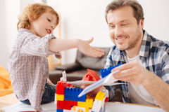 Positiver begeisterter bärtiger Mann, der mit seinem Kind spielt Stockbild