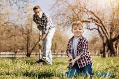 Positiver begeisterter blonder Junge, der mit Schaufel arbeitet Stockfoto