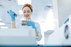 Positiver begeisterter blonder Laborassistent, der hinunter Reagens gießt Lizenzfreies Stockbild