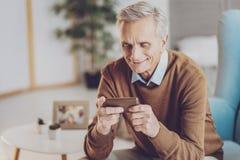 Positiver begeisterter Pensionär, der Telefon betrachtet stockbilder