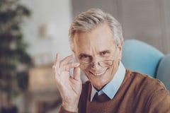 Positiver begeisterter Ruhestand, der auf Kamera lächelt lizenzfreies stockfoto