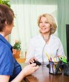 Positiver Doktor, der weiblichen Patienten konsultiert Lizenzfreie Stockfotos