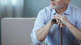Positiver erwachsener auf Sofa mit Spazierstock sitzender und entspannender Mann, Ruhestand stockfoto