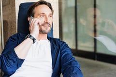 Positiver Geschäftsmann, der auf Mobiltelefon in Verbindung steht Lizenzfreie Stockfotografie