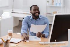 Positiver glücklicher Mann, der eine Computermaus hält Lizenzfreie Stockfotografie