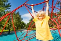 Positiver Junge mit den geraden Händen hängt am Seil Lizenzfreie Stockbilder