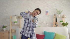 Positiver junger asiatischer Mann mit Gläsern im Wohnzimmer der Hauswurfsbanknoten stock video