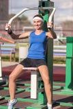 Positiver kaukasischer weiblicher Athlet im guten Sitz, der Training hat, übt im Freien mit Gewichten aus Stockfoto