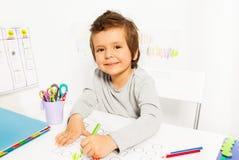 Positiver kleiner Junge zeichnet mit Bleistift während ABA Stockfotografie