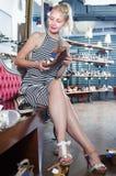 Positiver Kunde des jungen Mädchens, der auf Paaren Schuhen wählt Lizenzfreies Stockfoto