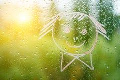 Positiver lustiger smiley auf regnerischem Herbstfenster Lizenzfreies Stockfoto