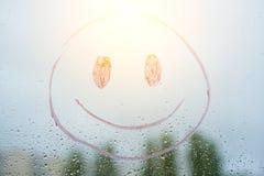 Positiver lustiger smiley auf regnerischem Herbstfenster Stockfoto