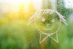 Positiver lustiger smiley auf regnerischem Herbstfenster Lizenzfreie Stockbilder