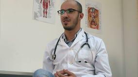Positiver männlicher Doktor im Büro sprechend mit Patienten stock video