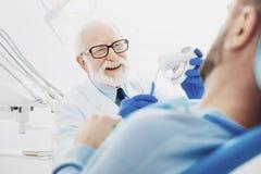 Positiver männlicher Zahnarzt, der sein Wissen teilt lizenzfreie stockbilder
