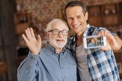 Positiver Mann, der Fotos mit seinem älteren Vater macht lizenzfreies stockbild
