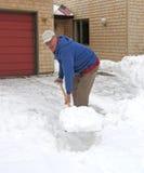 Positiver Mann, der Schnee schaufelt Stockfotos