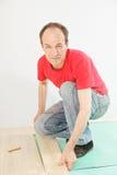 Positiver Mann im roten installierenden Bodenbelag Stockbilder