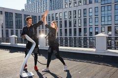 Positiver Mann und die Frau, die EMS-Kostüme trägt, rejoycing an den guten Ergebnissen lizenzfreies stockbild
