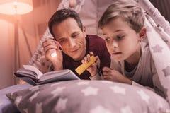 Positiver netter Vater und Sohn, die ein Buch liest Stockbilder