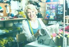 Positiver reifer Frauenschneider, der Nähmaschine verwendet Stockbild