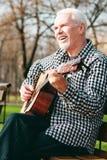 Positiver reifer Mann, der Gitarrenspiel studiert stockbilder