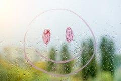 Positiver smiley auf einem regnerischen Herbstfenster Stockfotografie
