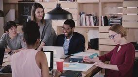 Positiver weiblicher Geschäftstrainer gibt dem multiethnischen Team Richtungen Chef der jungen Frau führt Bürositzungszeitlupe stock footage