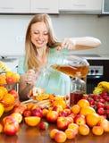 Positives blondes Mädchen, das frische Getränke gießt Stockfotos